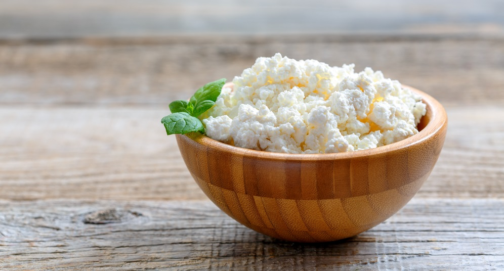 Homemade cottage cheese in a bowl on old wooden table