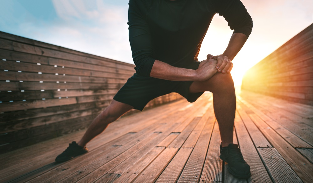 man stretching leg adductor muscles and warming up for training