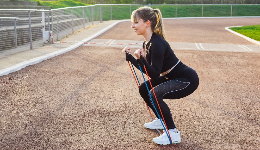 woman in sportswear doing deadlift exercise for glutes with resistance band