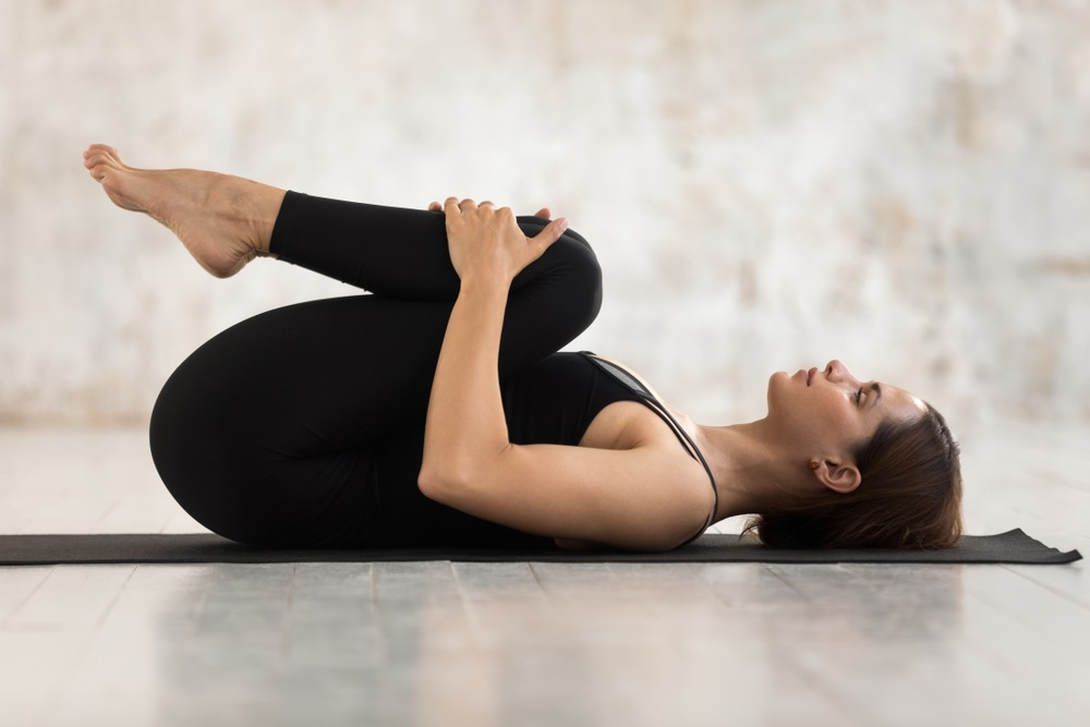 women relaxing in Knees to Chest pose